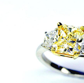 Trilogy ring with yellow cushion center diamond